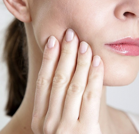 Woman with tooth pain and hand on cheek